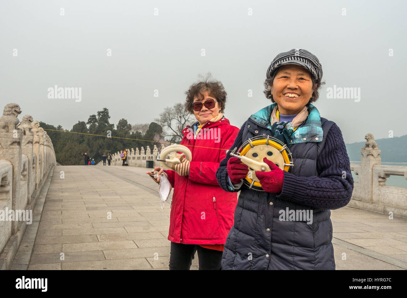 Two locals smiling: Chinese women flying kites on the 17 Arch Bridge (Shiqi Kong Qiao) leading to South Lake Island, - Stock Image