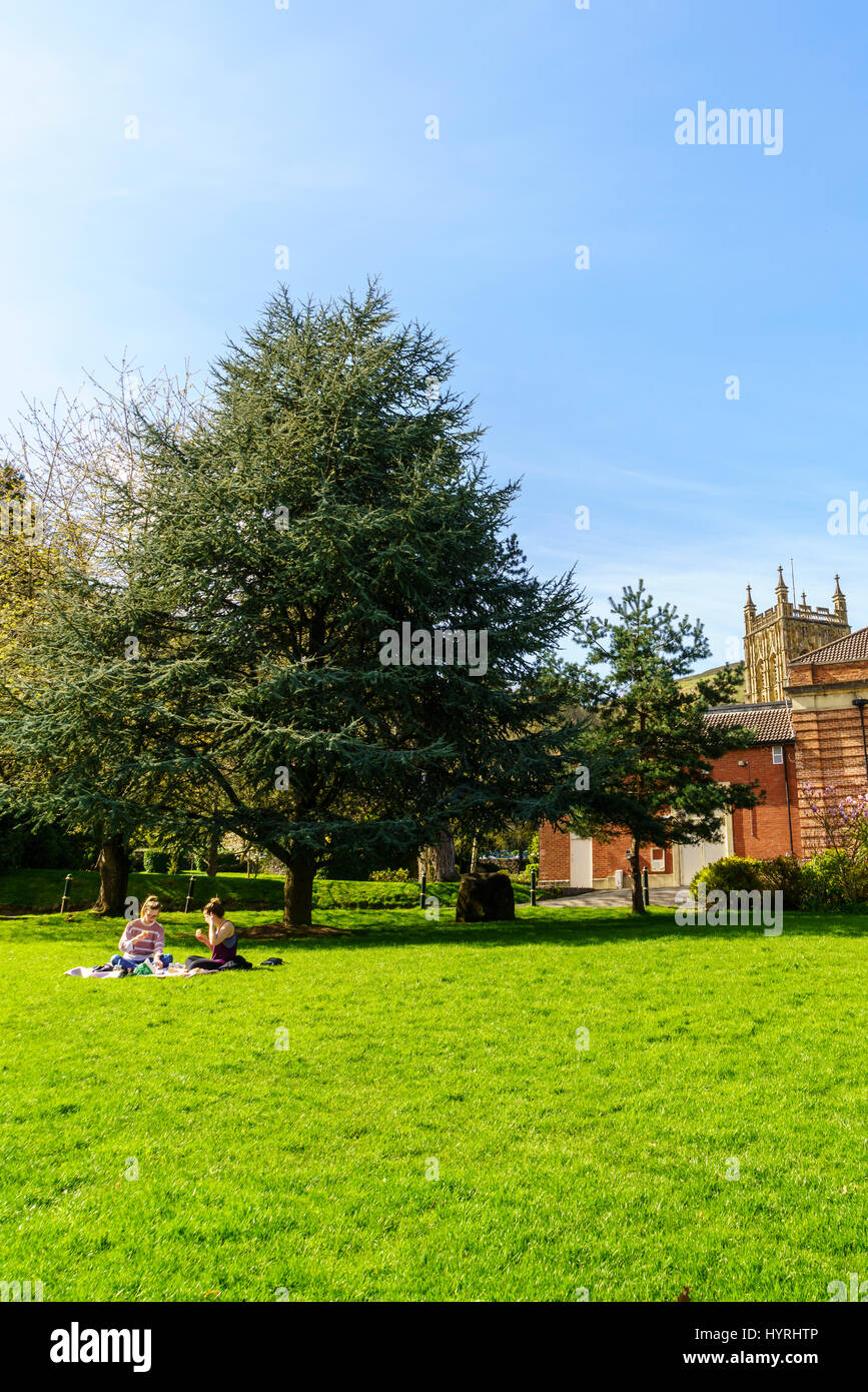 Two young women picnicking on the grass in a park in springtime. - Stock Image