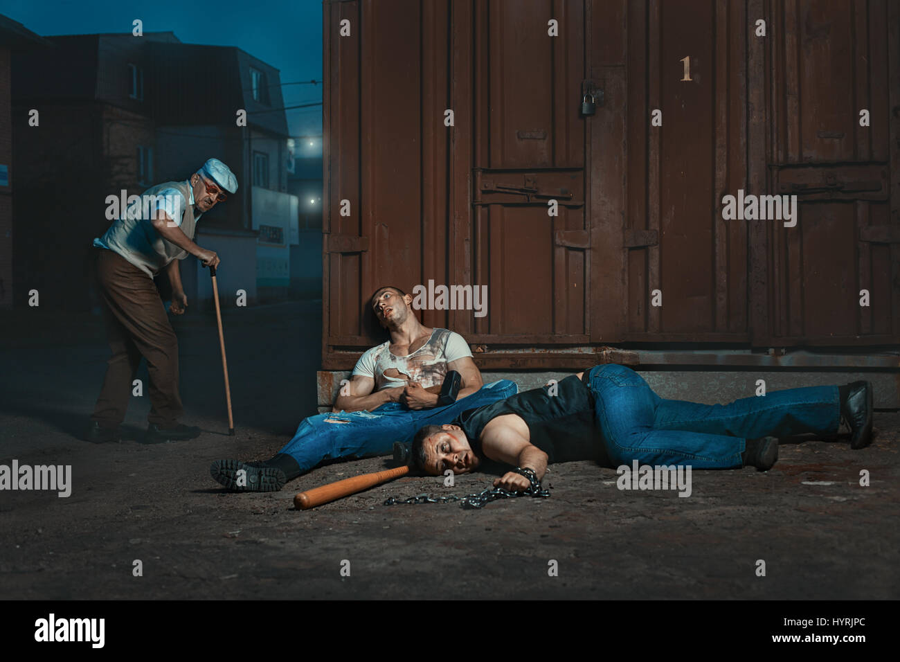 Old man beaten by thugs on the street at night. - Stock Image