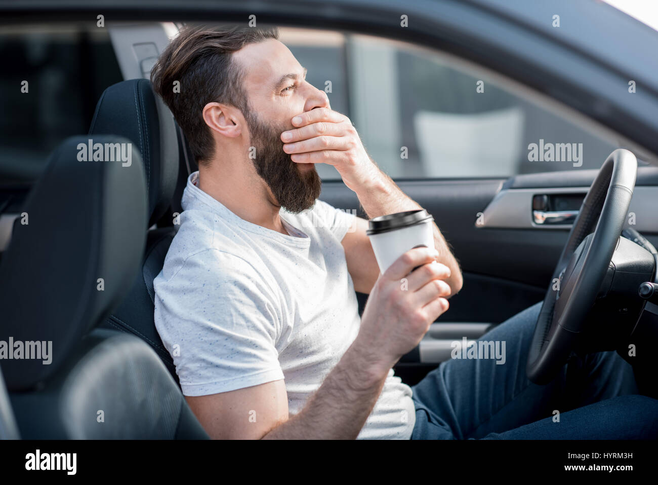 Tired man driving a car - Stock Image