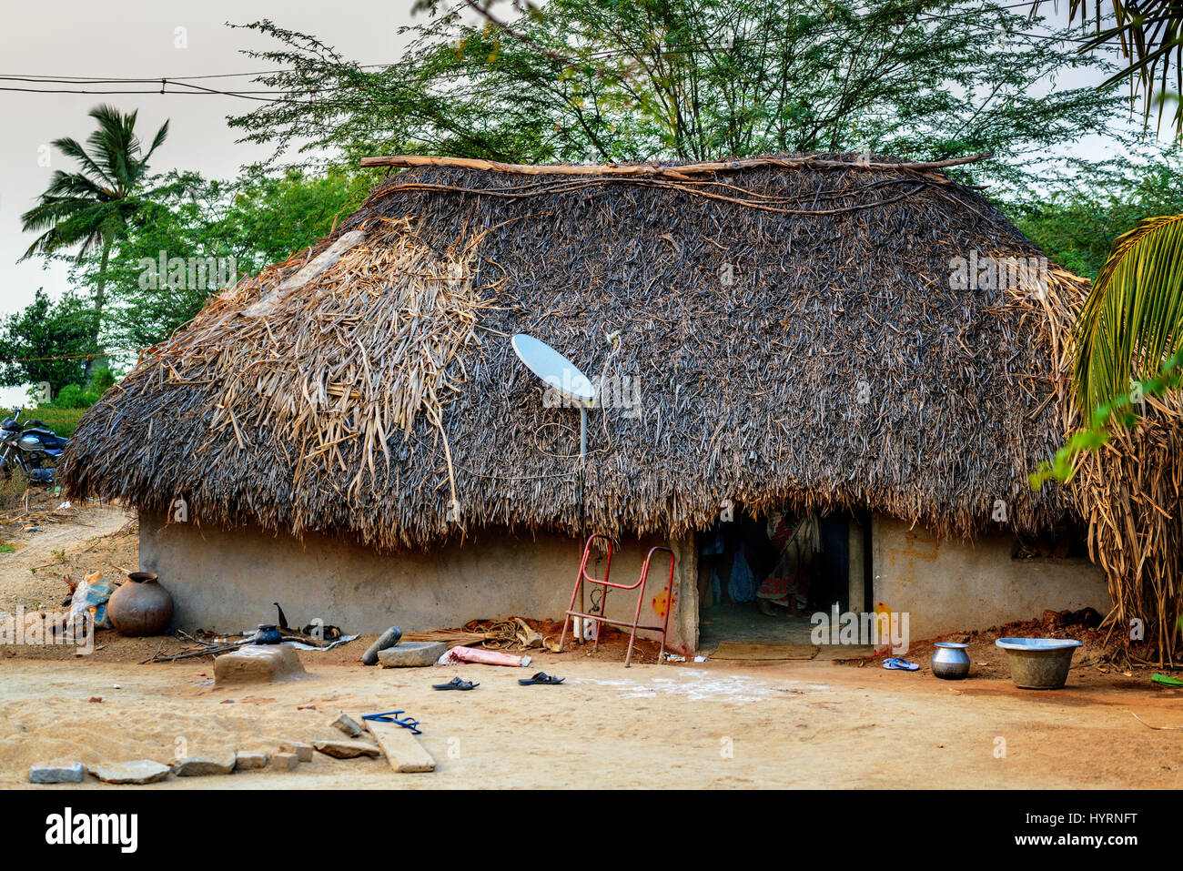 Traditional thatch hut with satellite TV dish - Stock Image