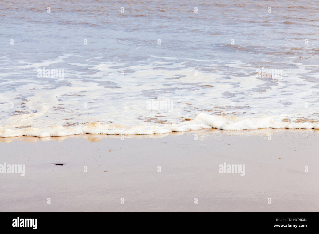 Sea foam or spume on the tide flowing across the sand on a beach - Stock Image