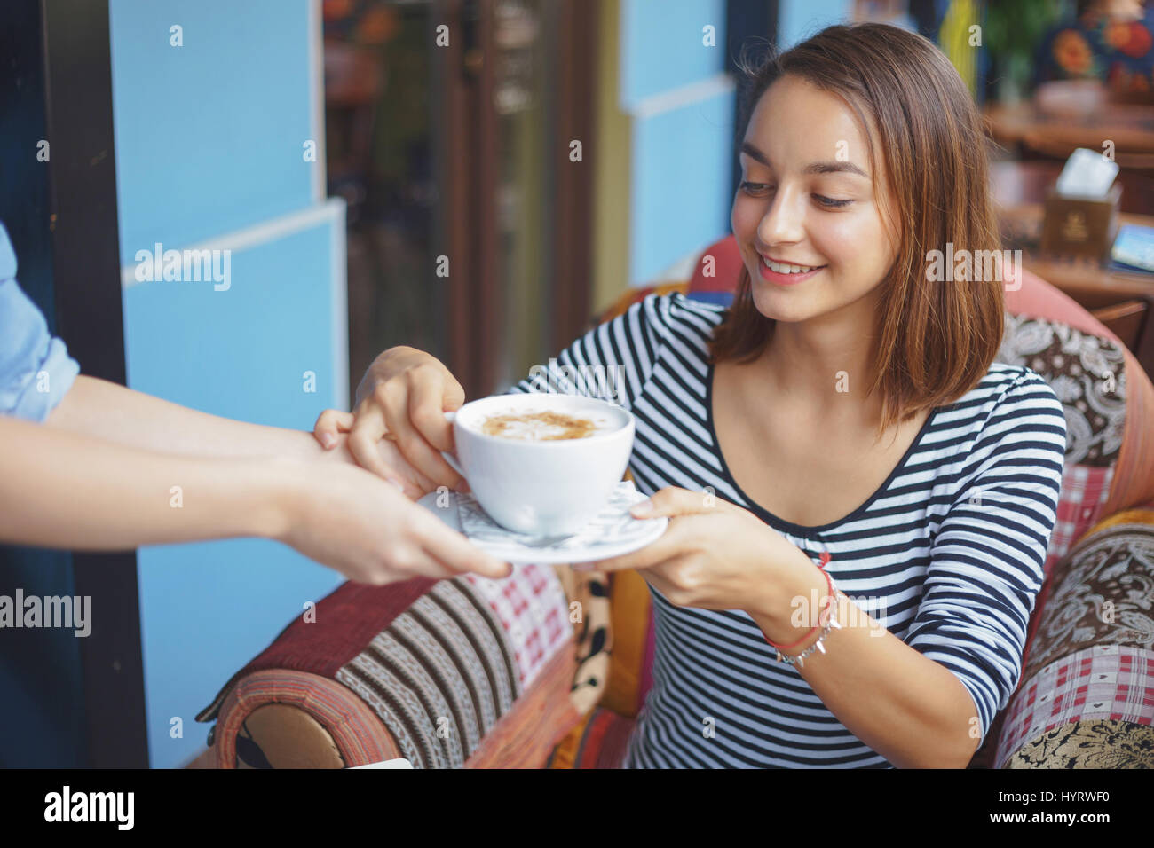 Young woman sitting indoor in urban cafe. Cafe city lifestyle. Casual portrait of teenager girl - Stock Image
