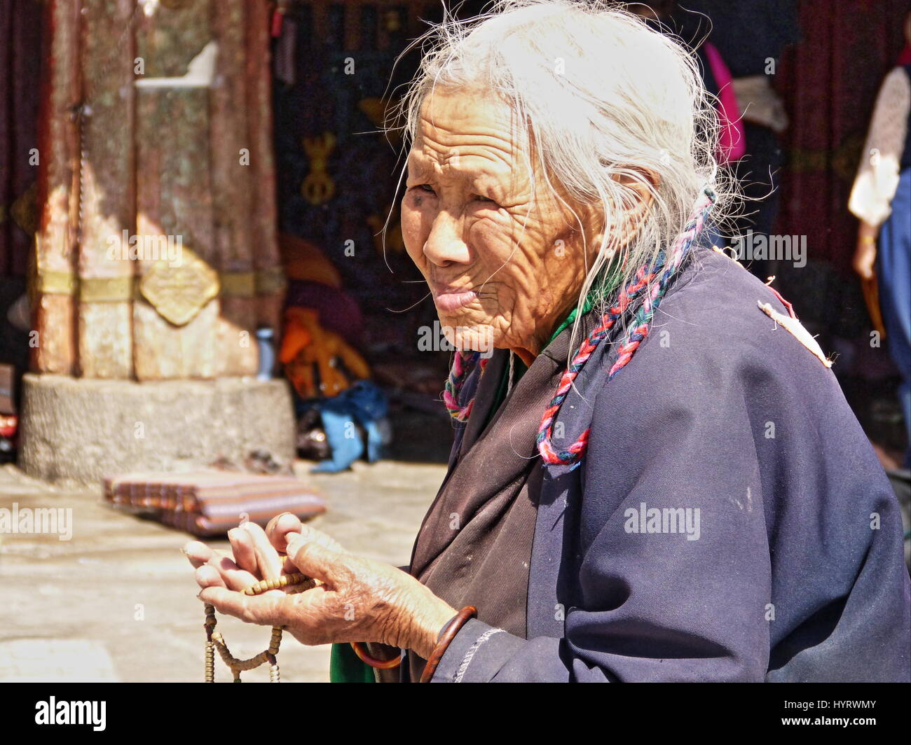 A old Tibet woman with her prayer beads in front of Jokhang Temple, also known as Qoikang Monastery or Jokhang Monastery - Stock Image