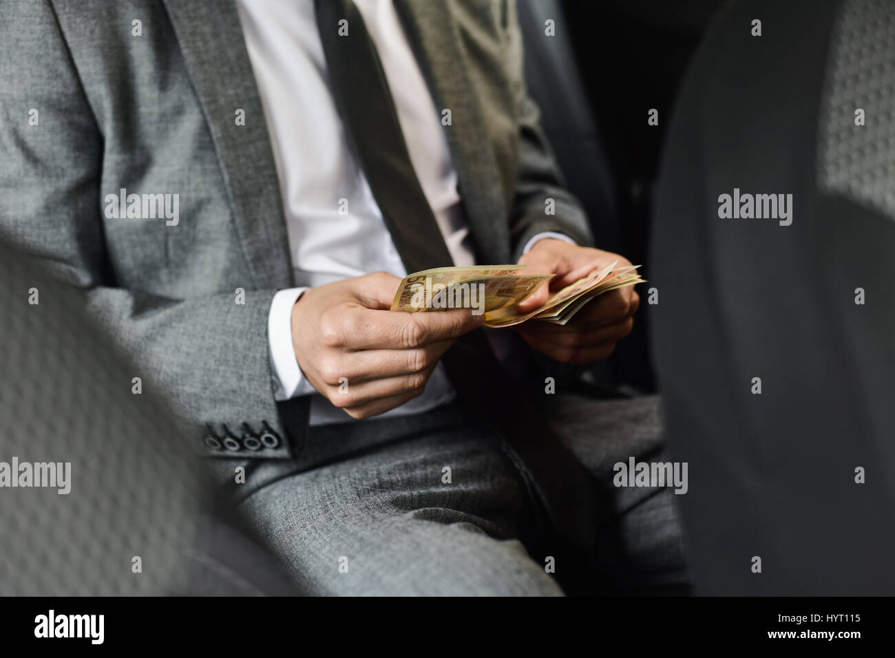 a young caucasian man in an elegant gray suit counts euro bills sitting in the back seat of a car Stock Photo