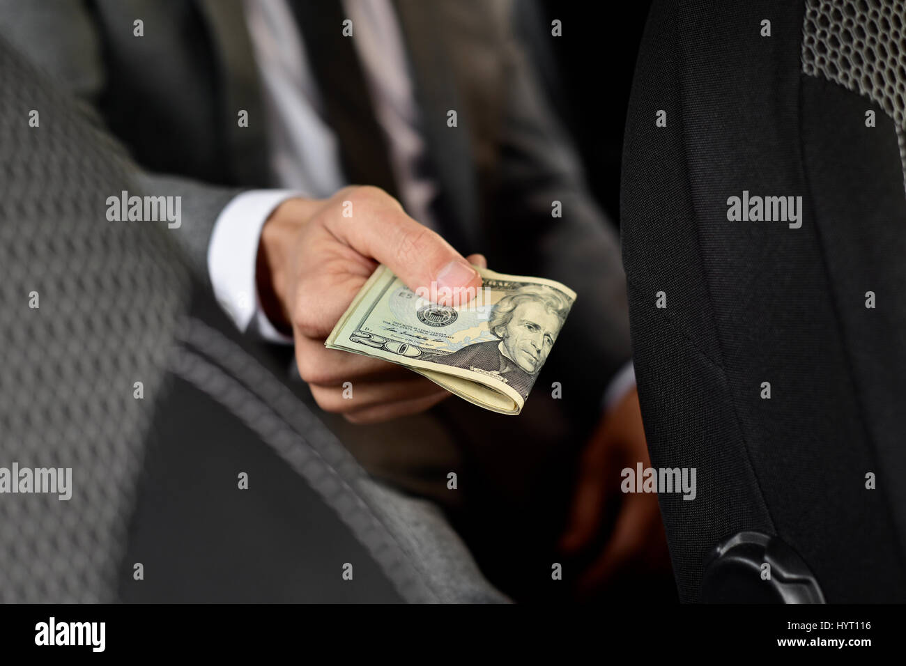 a young caucasian man in an elegant gray suit sitting in the back seat of a car offers a wad of dollar bills to Stock Photo