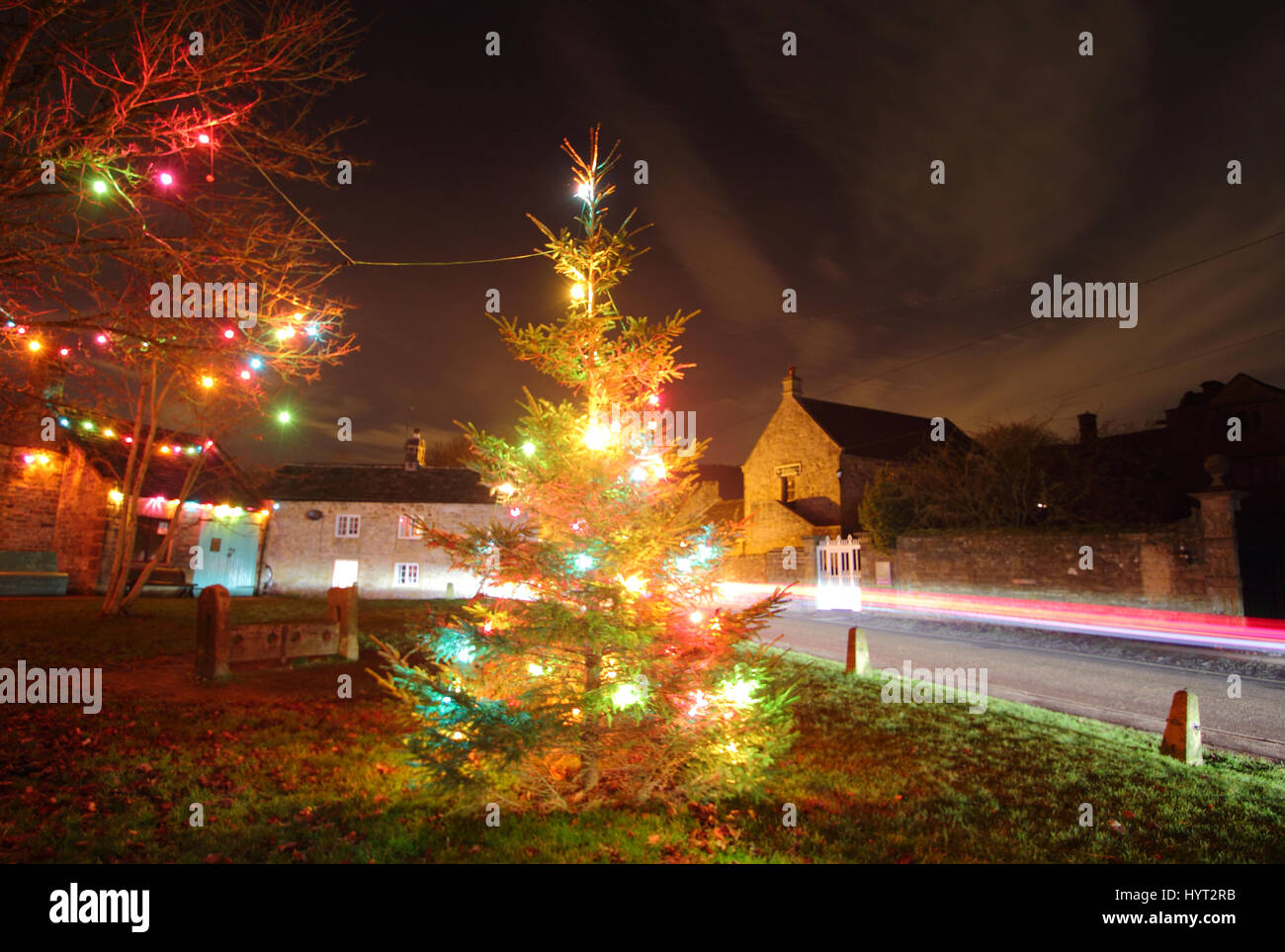 Christmas decorations by the wooden stocks opposite Eyam Hall (right) in Eyam; the pretty and historic 'plague - Stock Image