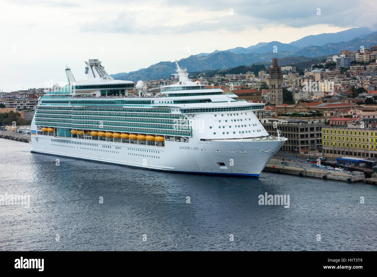 Navigator of the Seas (Royal Caribbean Cruise Lines) cruise ship docked at port and overlooking the town of Messina. - Stock Image