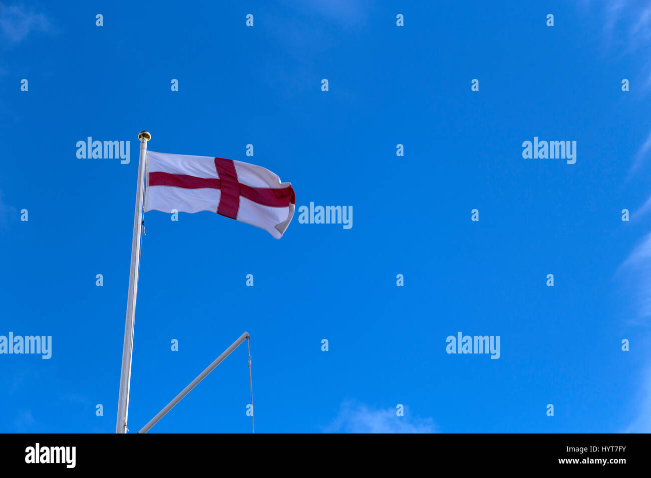 St Georges flag flying against a blue sky from a gold topped flagpole. - Stock Image