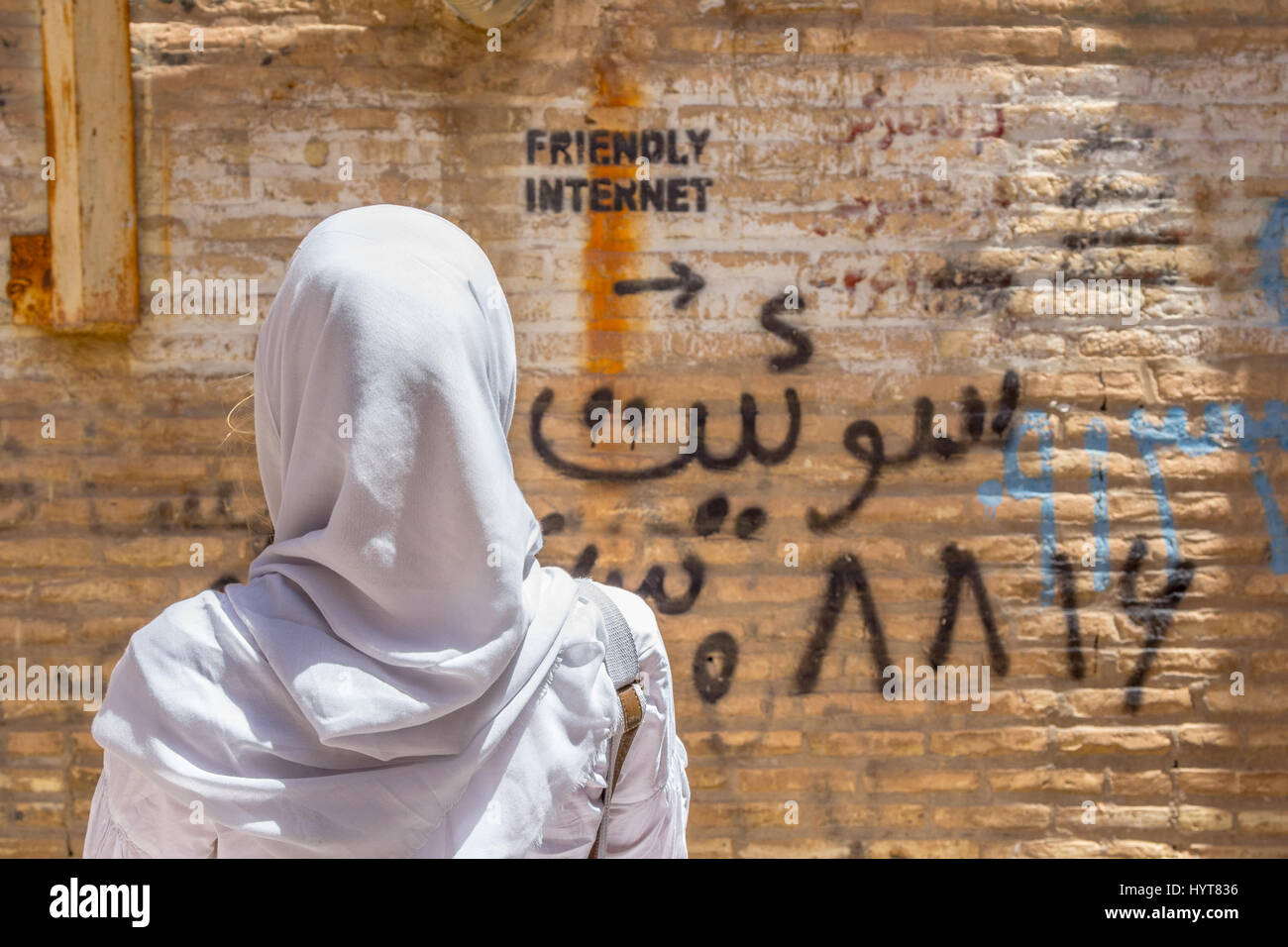 YAZD, IRAN - AUGUST 18, 2016: Veiled woman looking at an inscription on the wall indicating uncensored Internet - Stock Image