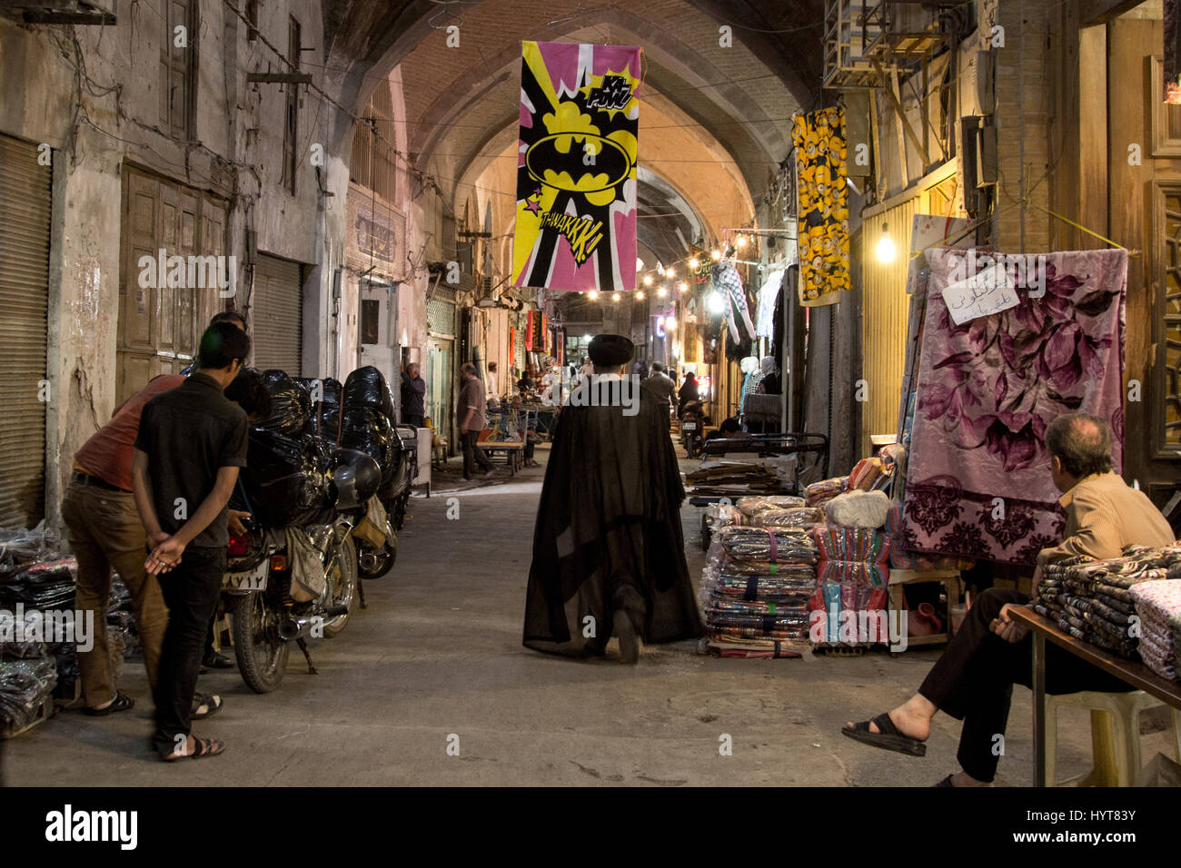 ISFAHAN, IRAN - AUGUST 20, 2016: Imam passing under a Batman logo in Isfahan bazaar  Picture of an Iranian imam - Stock Image