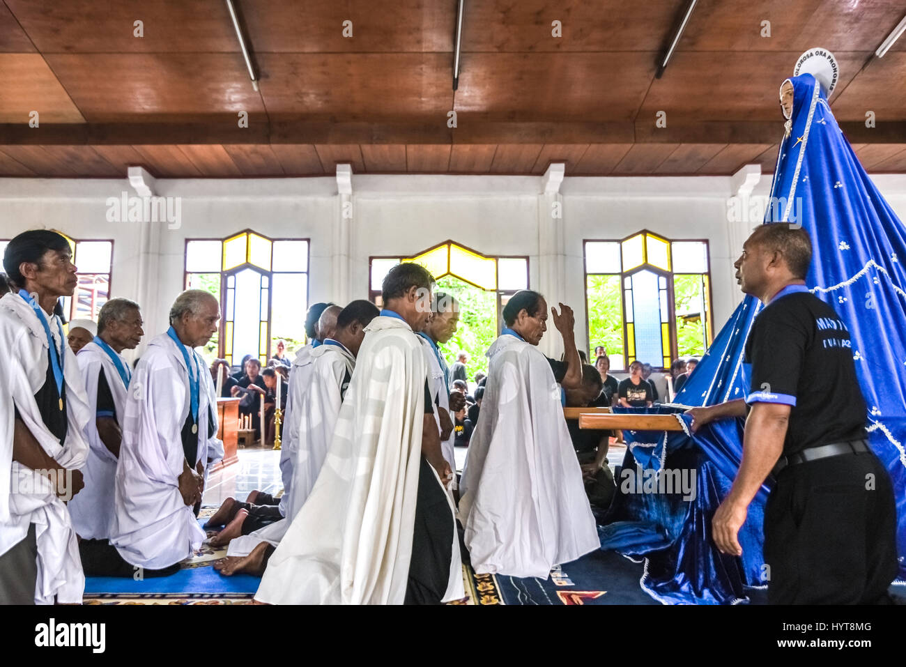 Elders of the Tuan Ma chapel pray in front of ancient Tuan Ma (Mother Mary) statue during Holy Week procession in - Stock Image
