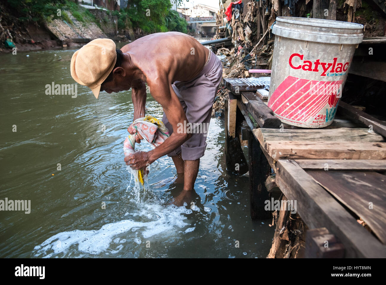 A man washes a towel on the Ciliwung River in Bukit Duri area, Jakarta, Indonesia. © Reynold Sumayku - Stock Image