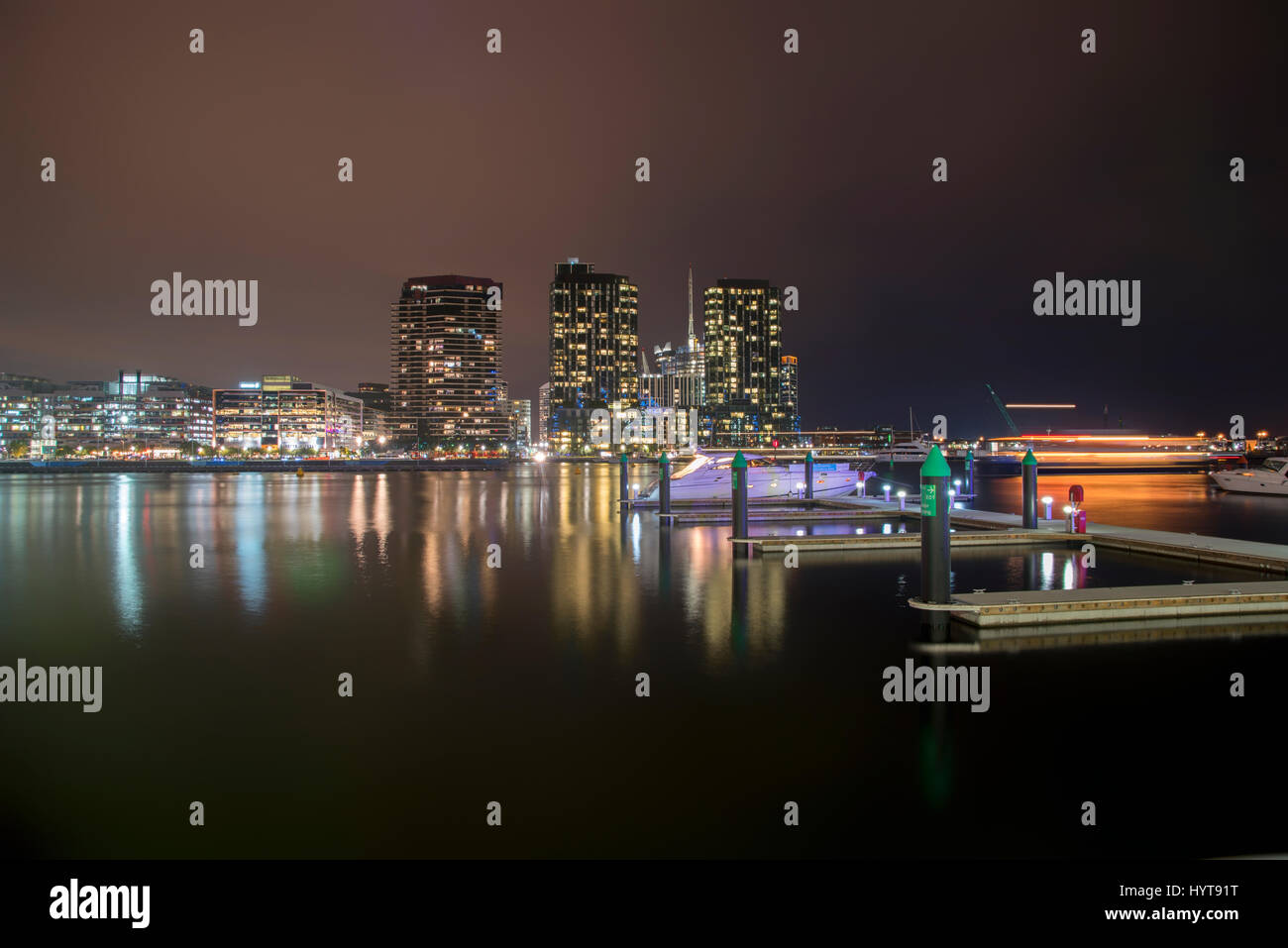 A beautiful view of a city by the sea with colorful lights and marina with private boats anchored at night. - Stock Image