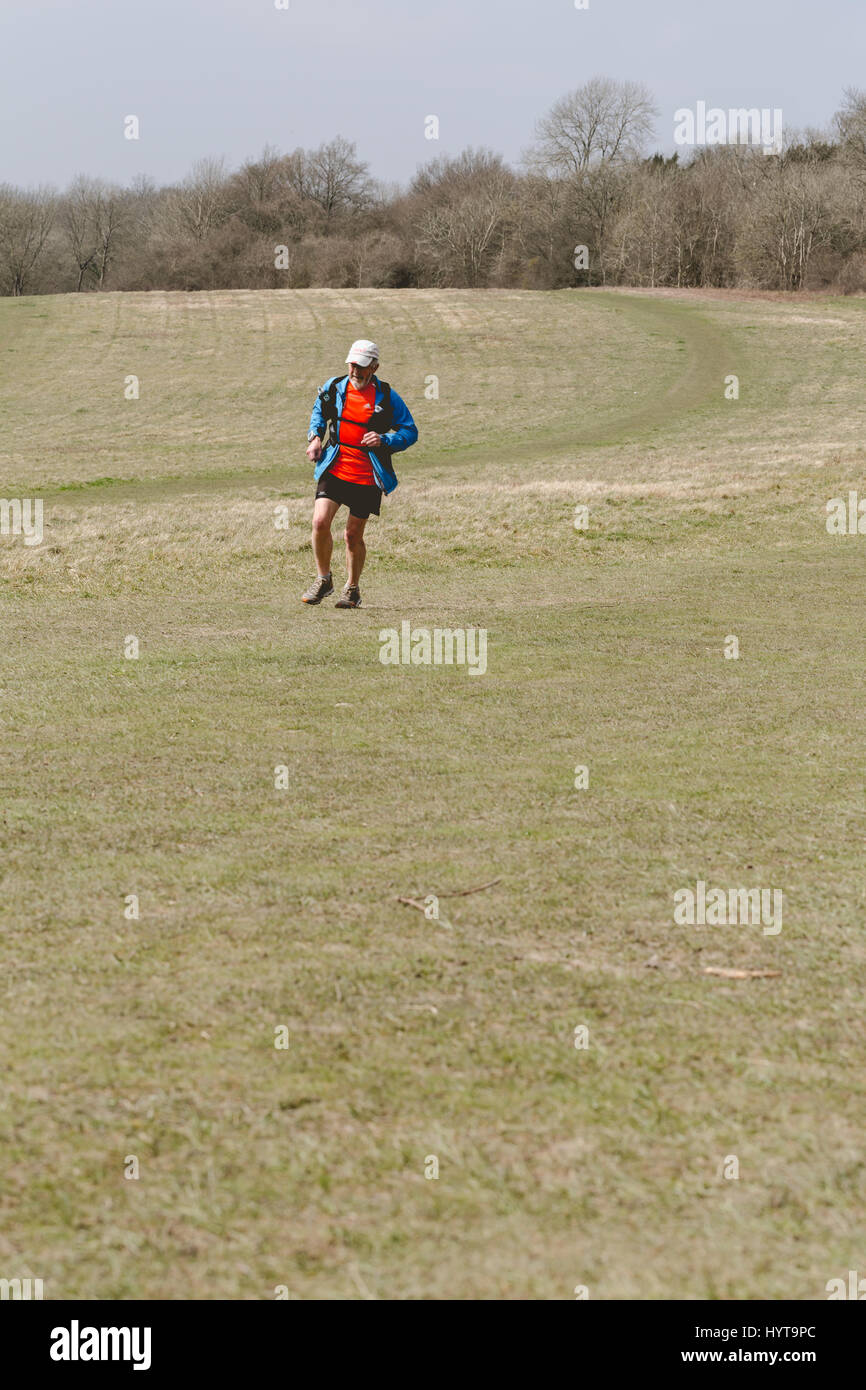 Older man with rucksack running through Surrey fields and meadows - Stock Image