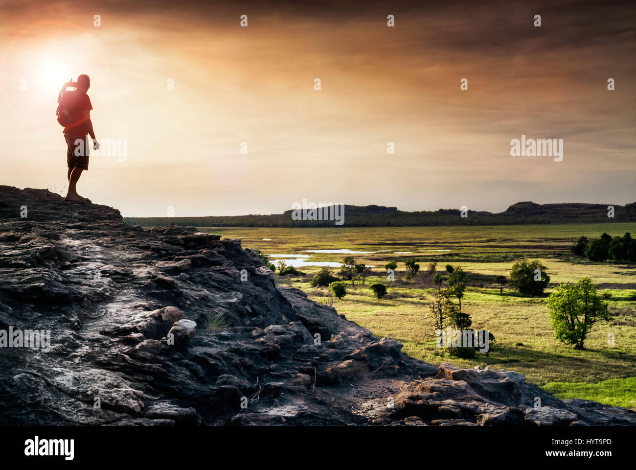 Lone figure watches the sunset from Ubirr rock looking down at the Nadab floodplains. Northern Territory, Australia Stock Photo
