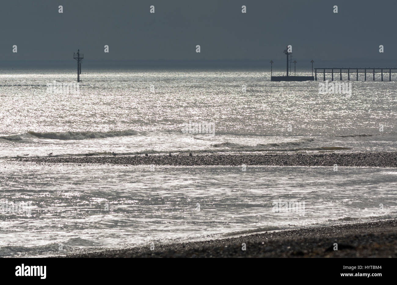 Sea glistening with reflections from the sun, looking out to dark stormy skies. - Stock Image
