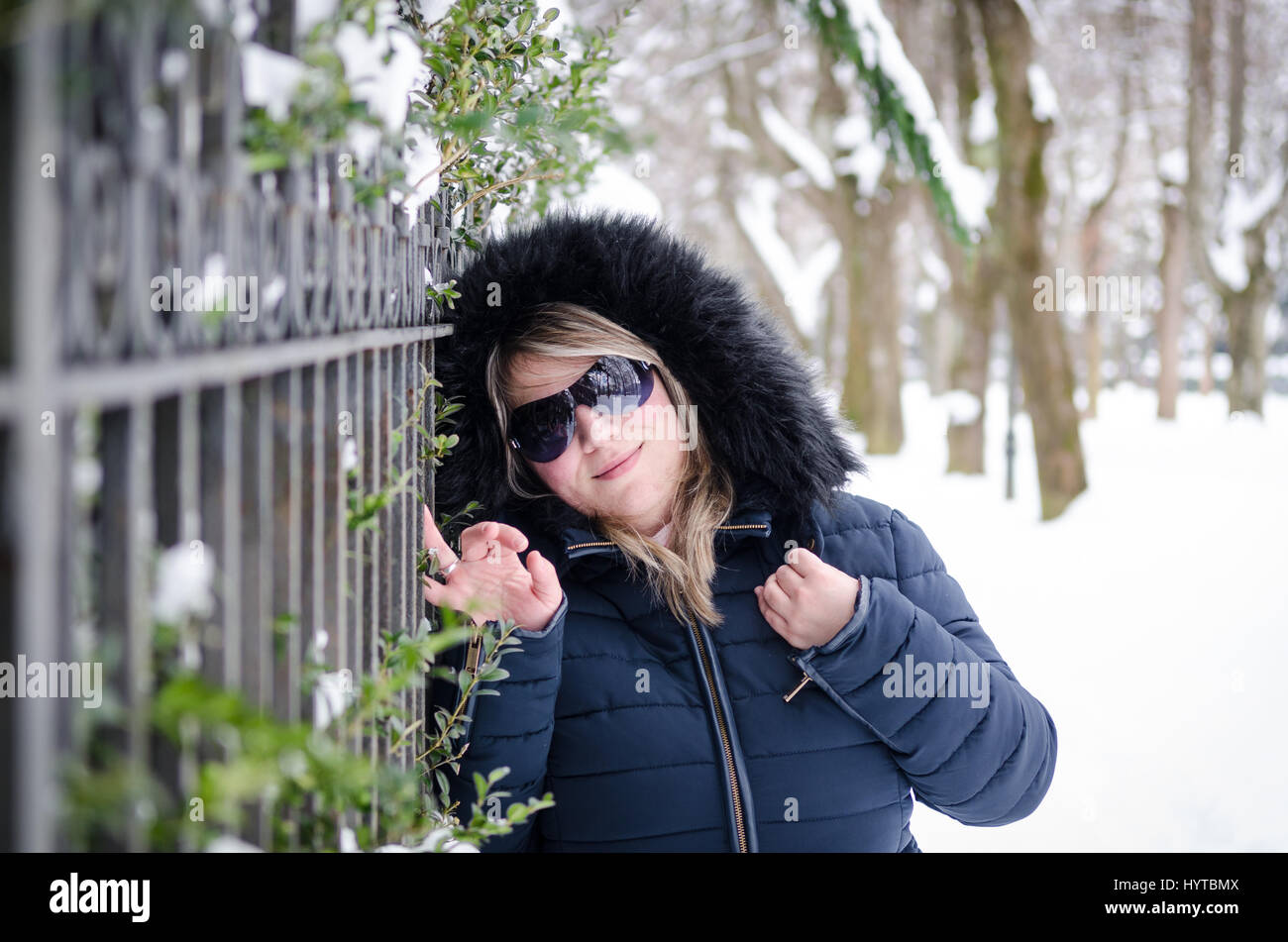 Portrait of a young beautiful woman with a fur hood and sunglass in the park on the snow - Stock Image