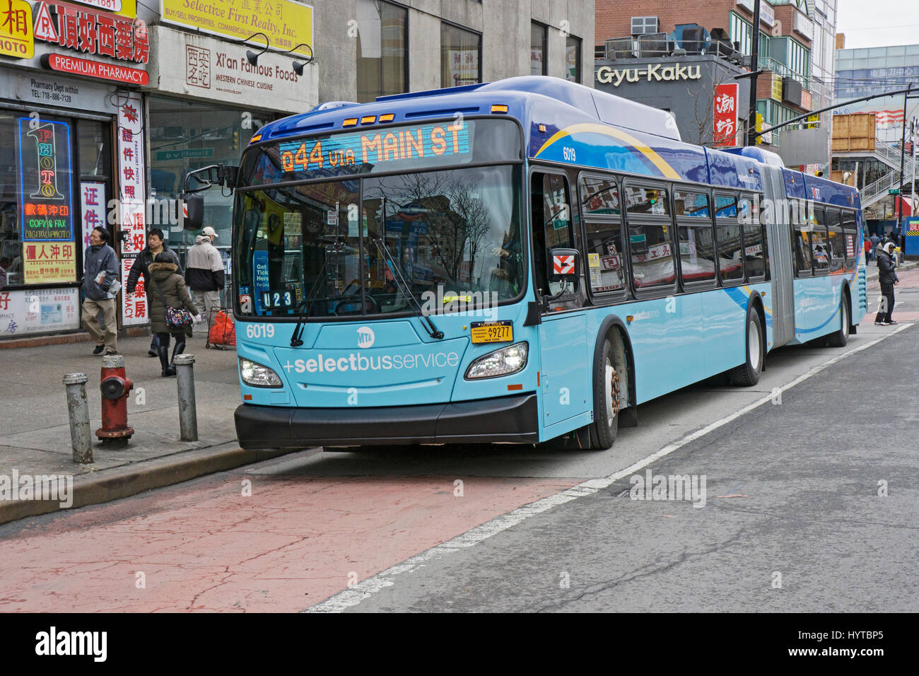 New style New York City easy-entry articulated bus on Main Street in Chinatown, Flushing, Queens, New York City. - Stock Image