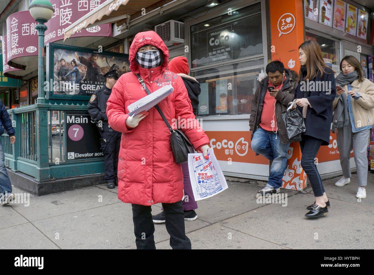 An Asian American woman wearing a surgical mask handing out leaflets on a cold early spring morning. In Chinatown, - Stock Image