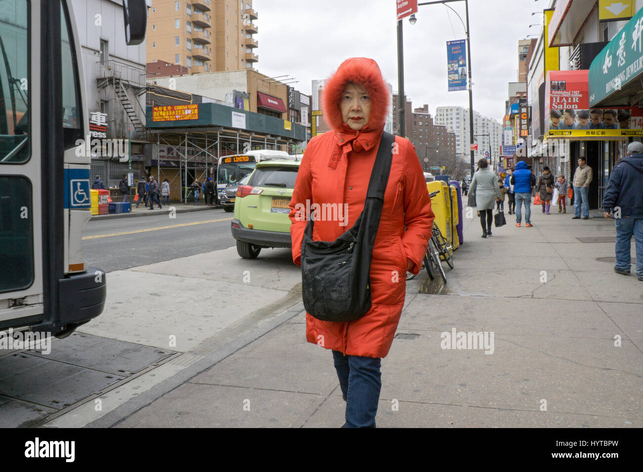 A Chinese American woman in a red hooded coat walking down Main Sreet in a cold early Spring day. In CHinatown, - Stock Image