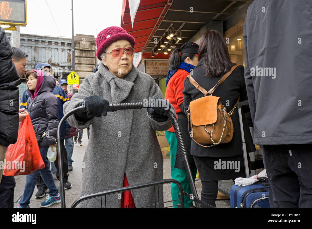 An older Chinese American woman outside shopping on a cold day on Main Street in Chinatown, Flushing, Queens, New - Stock Image