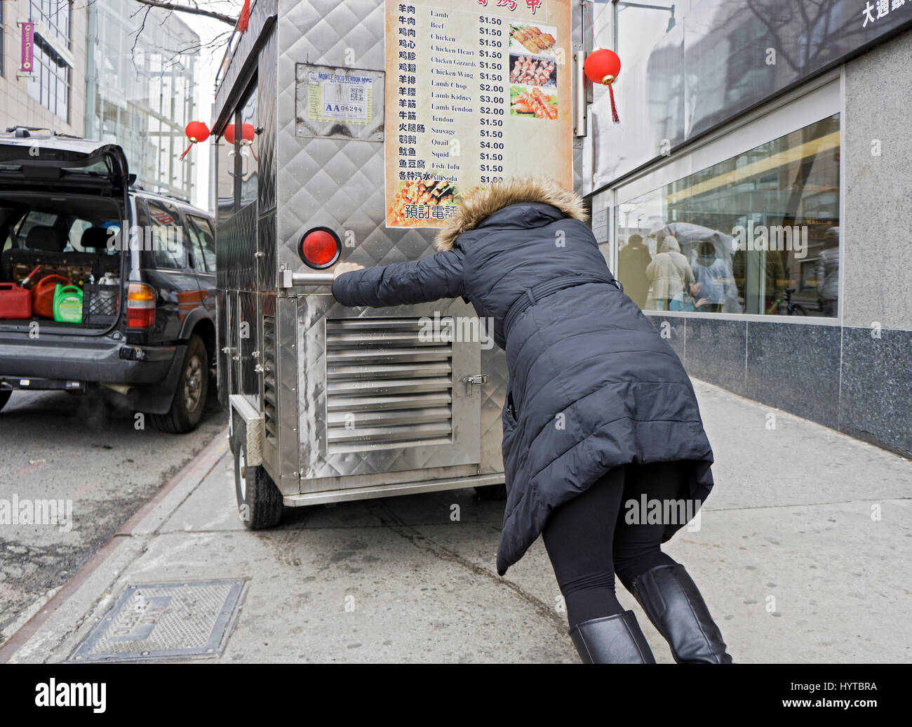 A Chinese American woman pushing a food cart into place on a street in Chinatown, Flushing, Queens, New York City - Stock Image