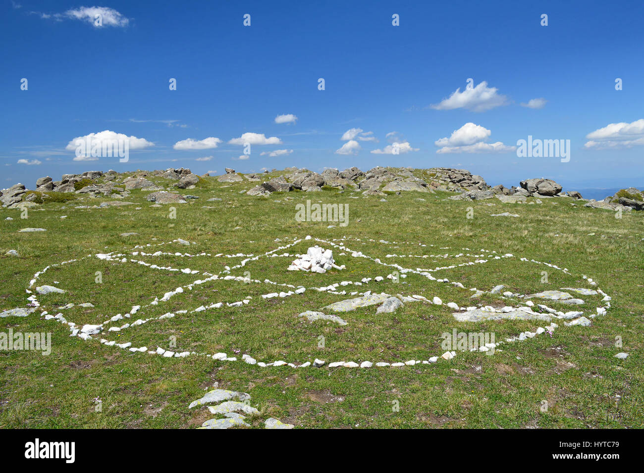 Drawn by white stones on the green grass circle with pentagram in it - the spiritual symbol of The White Brotherhood, - Stock Image