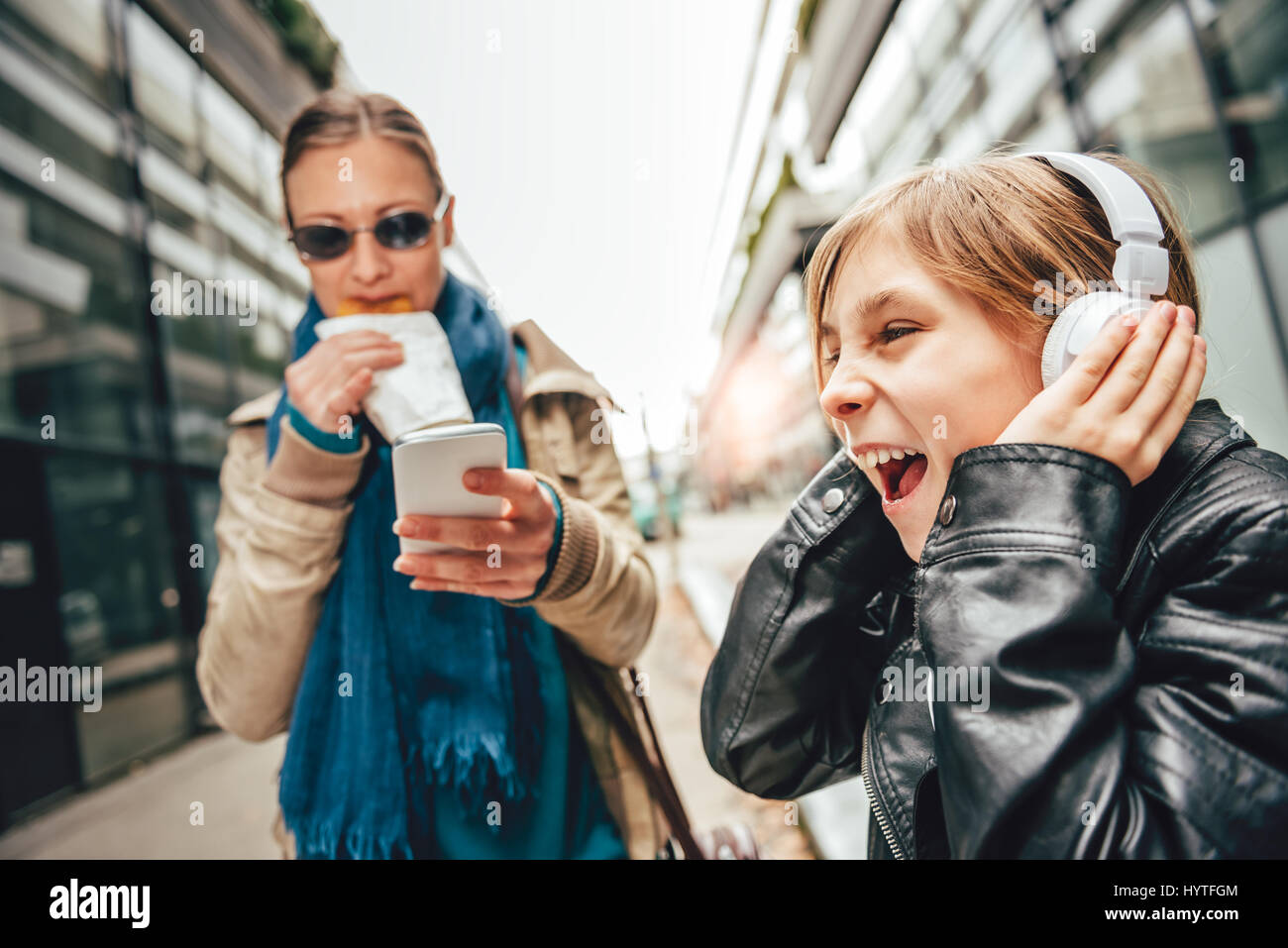 Daughter listening music on headphones with mother standing beside eating and using smart phone - Stock Image