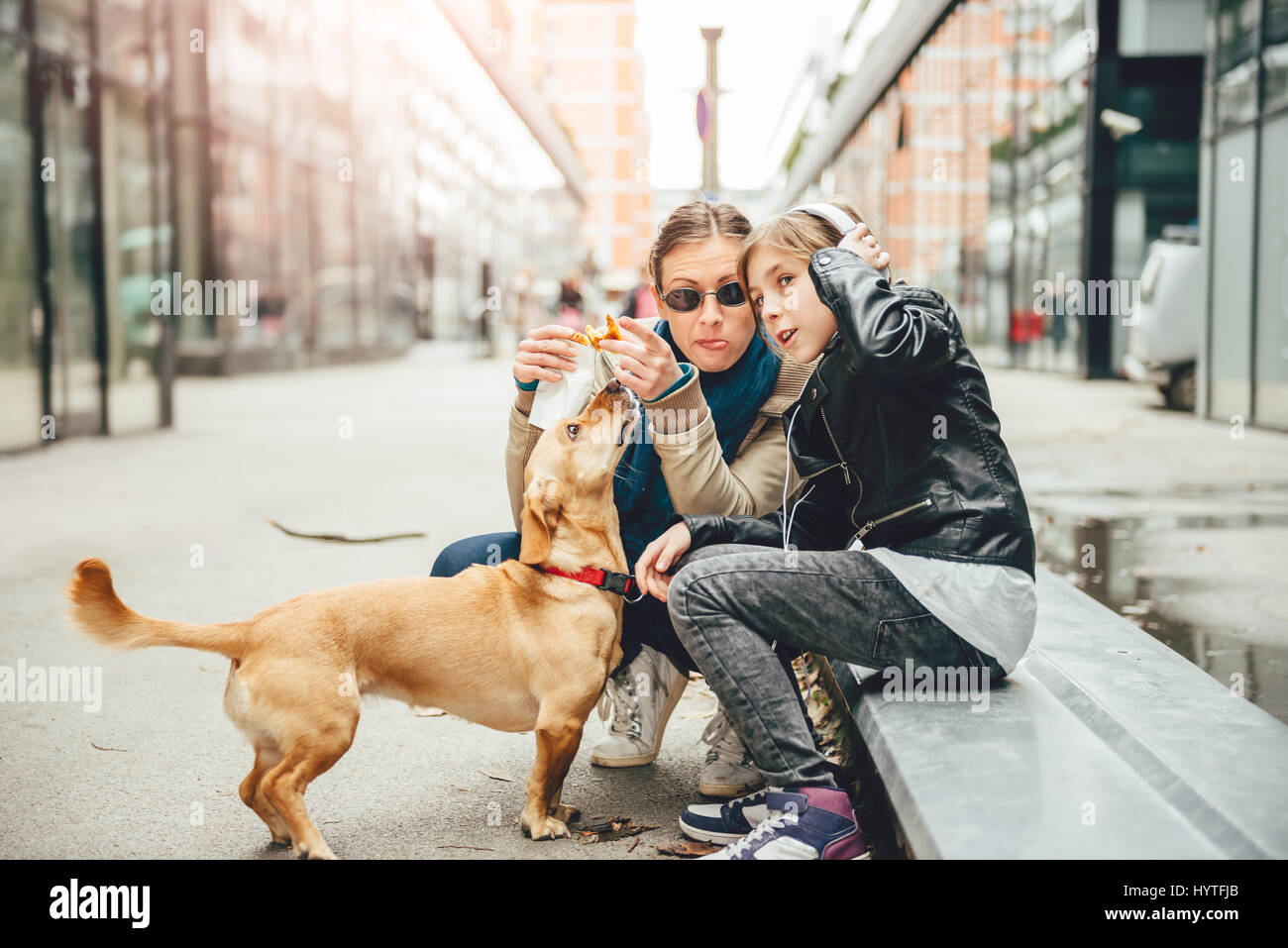 Mother eating sandwich and petting a dog while daughter listening to music on the street - Stock Image