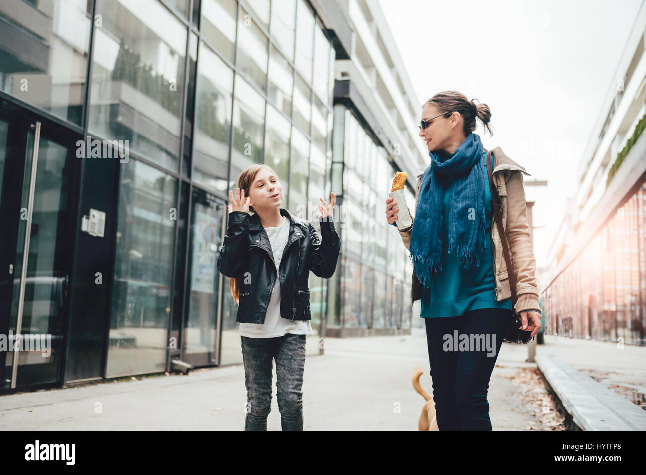 Mother and daughter walking down the city streets and eating sandwich - Stock Image