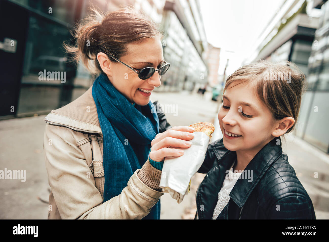 Mother walking down the city and daughter sharing sandwich - Stock Image