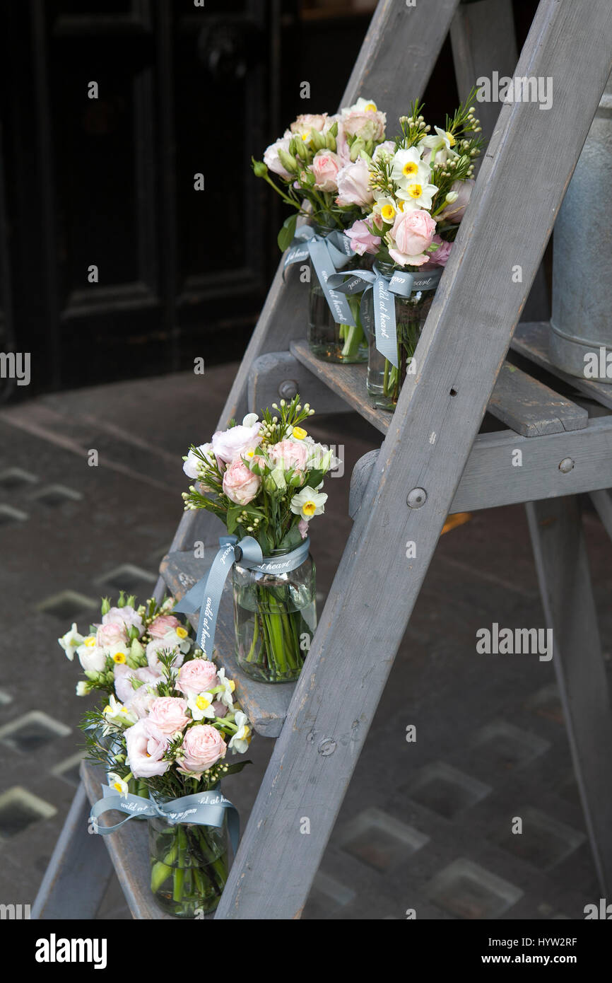 A bouquet of lisianthus, roses and carnations on the steps of the staircase as decoration of the entrance to the - Stock Image