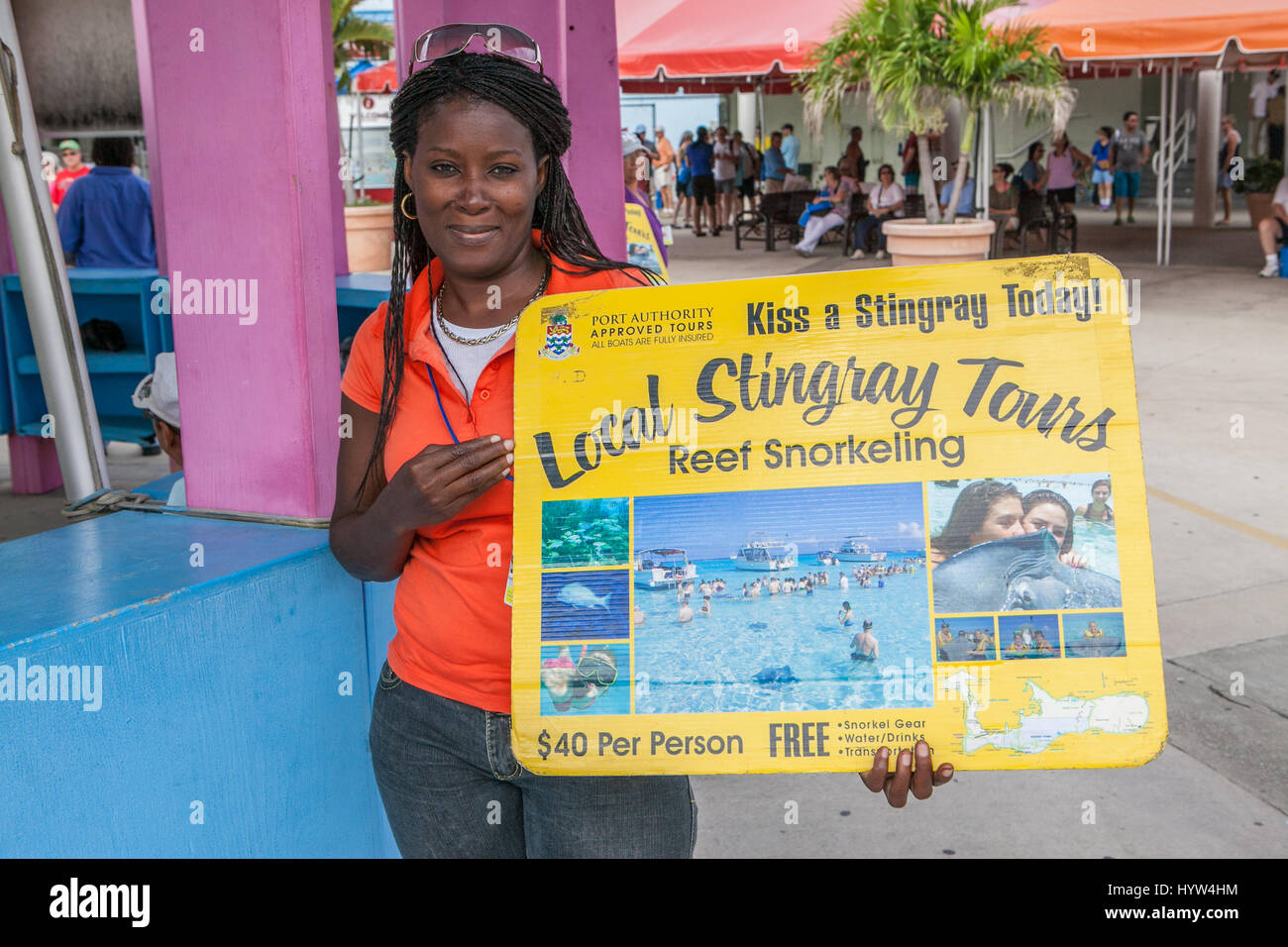 Young local woman selling tours of Sting Ray City Cayman Islands - Stock Image