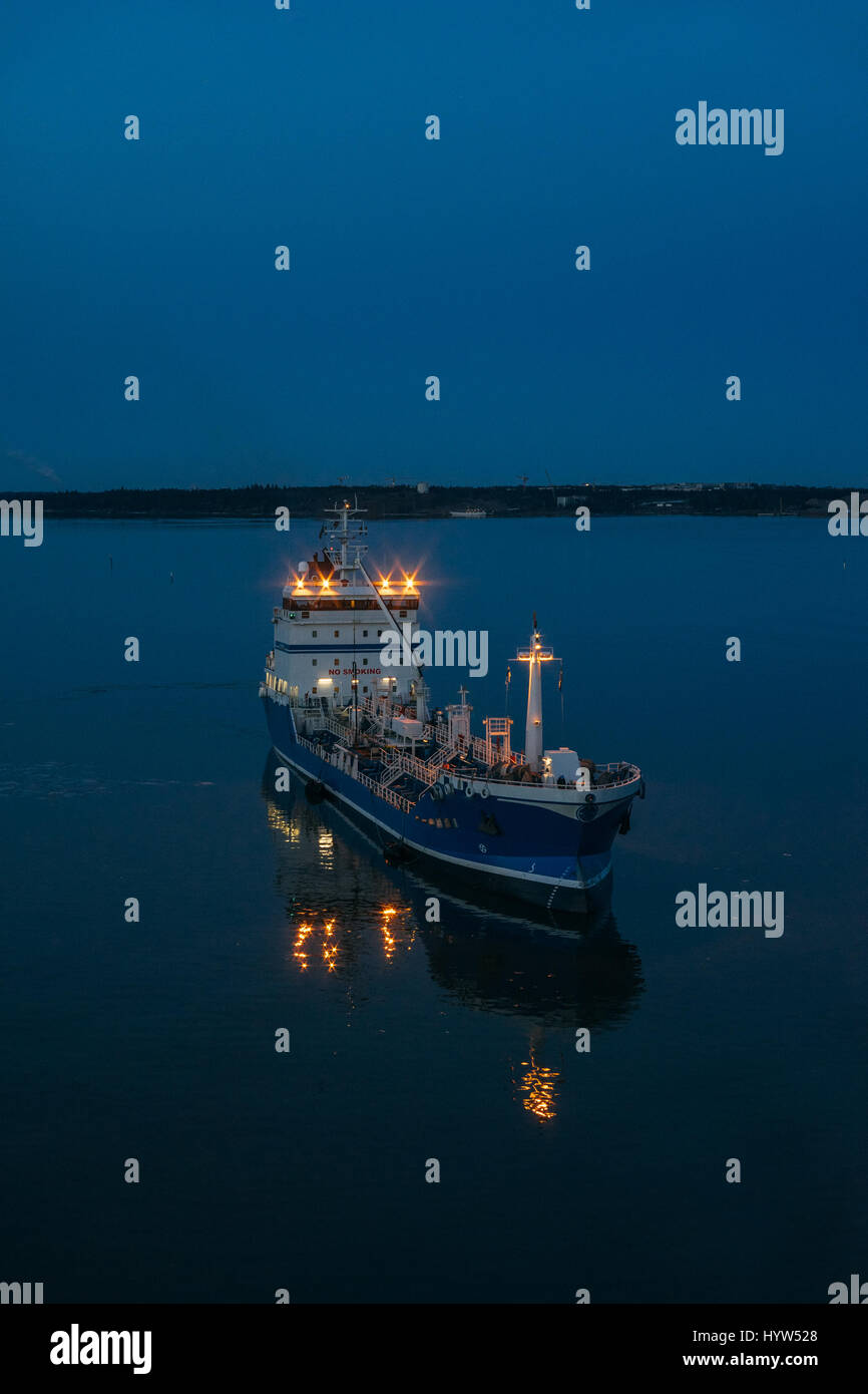 Cargo ship leaves port and sailing into open sea, twilight scene - Stock Image