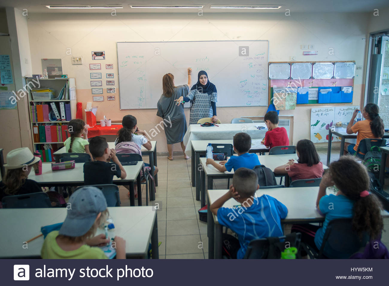 Alia Hussien addresses the class of 3rd Graders while her fellow teacher Efrat Toval writes on the black board. - Stock Image