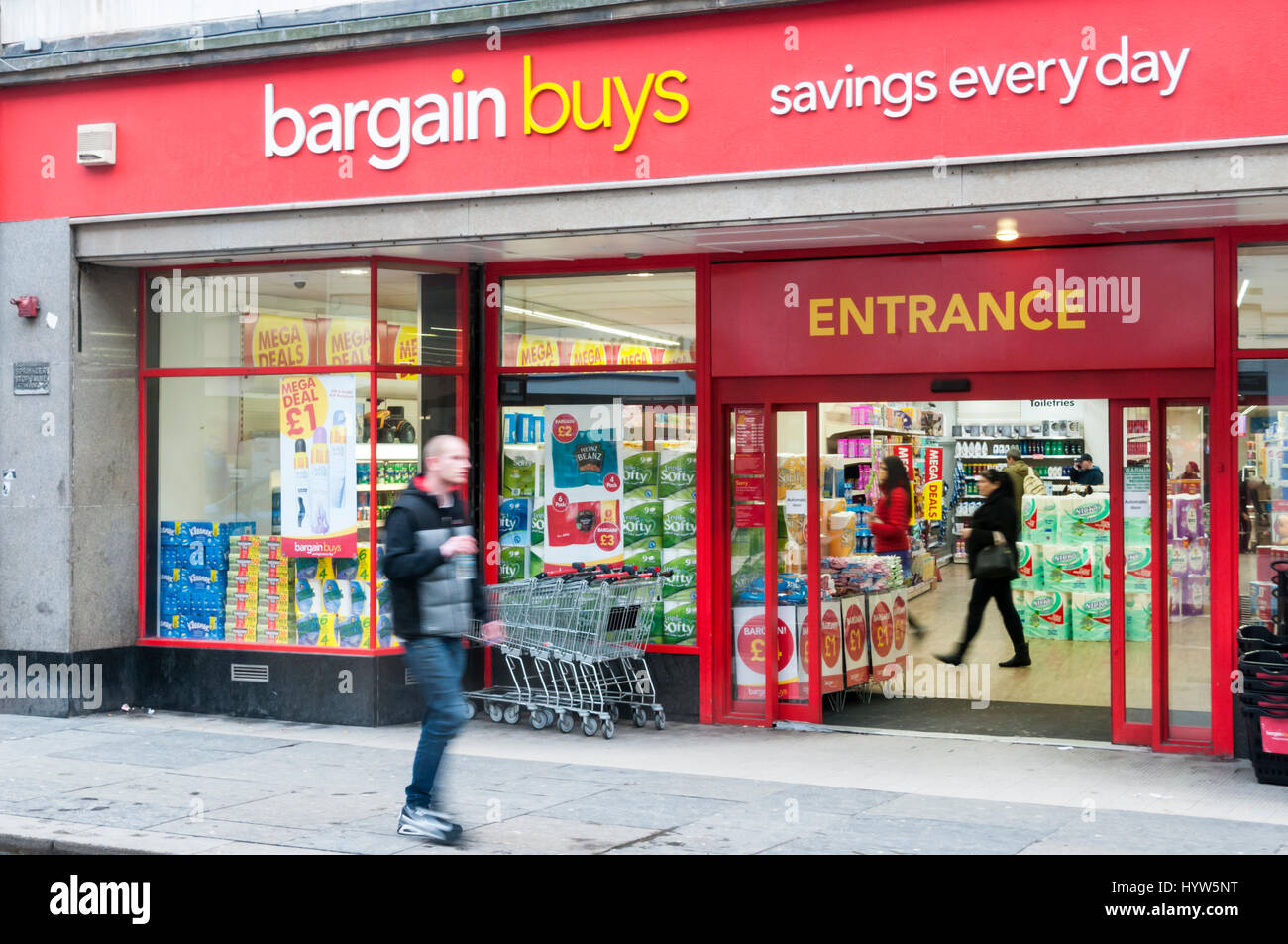 A man (motion blurred) walks past a branch of Bargain Buys in Newcastle Upon Tyne. - Stock Image