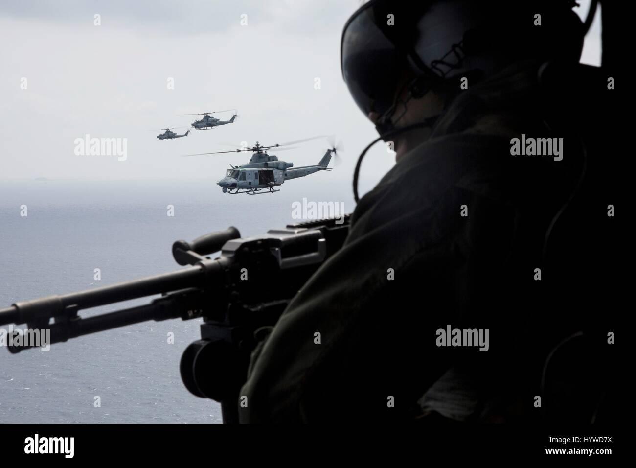 Owinawa, Japan. 26th Apr, 2017. U.S. Marine Corps Sgt. Mark Alvarez, mans the door gun on a UH-1Y Huey helicopter, Stock Photo