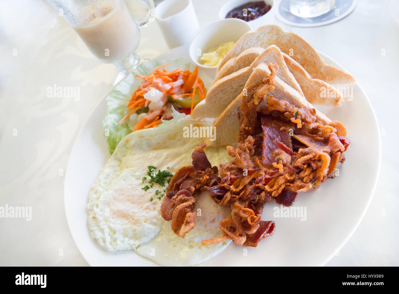 Bacon and fried egg breakfast in setting - Stock Image