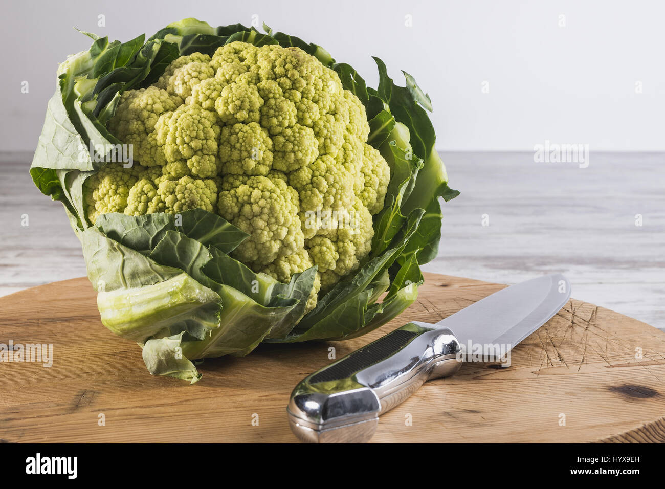 green cauliflower on a cutting board with knife - Stock Image