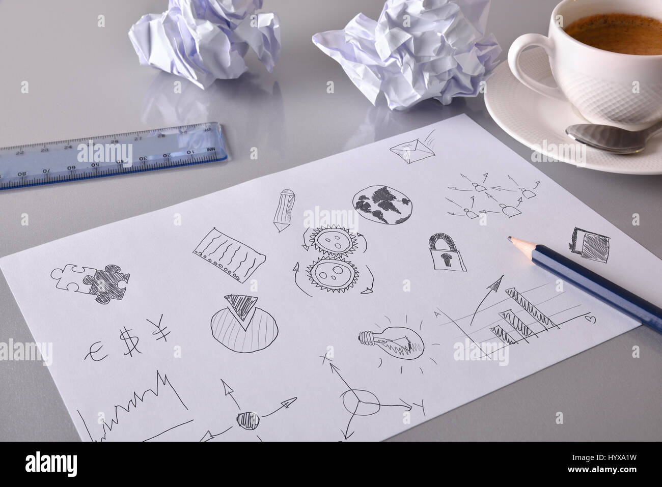 Sheet with drawings of relevant business concept on gray office table with crumpled sheets and coffee in the background. - Stock Image