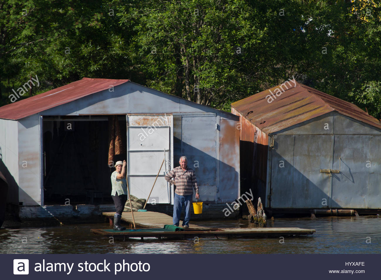 A man and woman pause in their work to watch a tour boat pass on the Sheksna River in Russia. - Stock Image