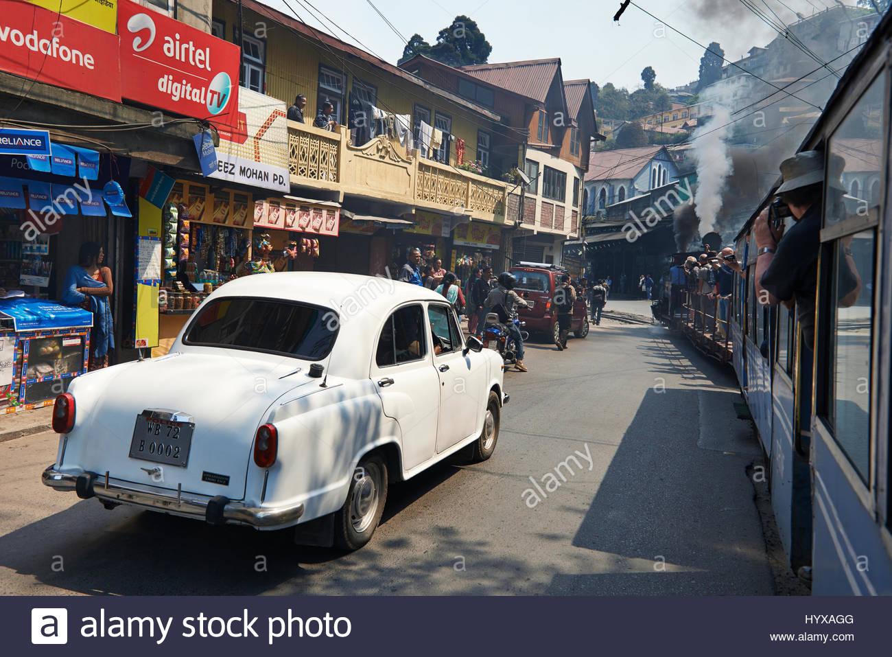 A Hindustan Ambassador, a car manufactured by Hindustan Motors of India, drives down a street alongside the Darjeeling - Stock Image