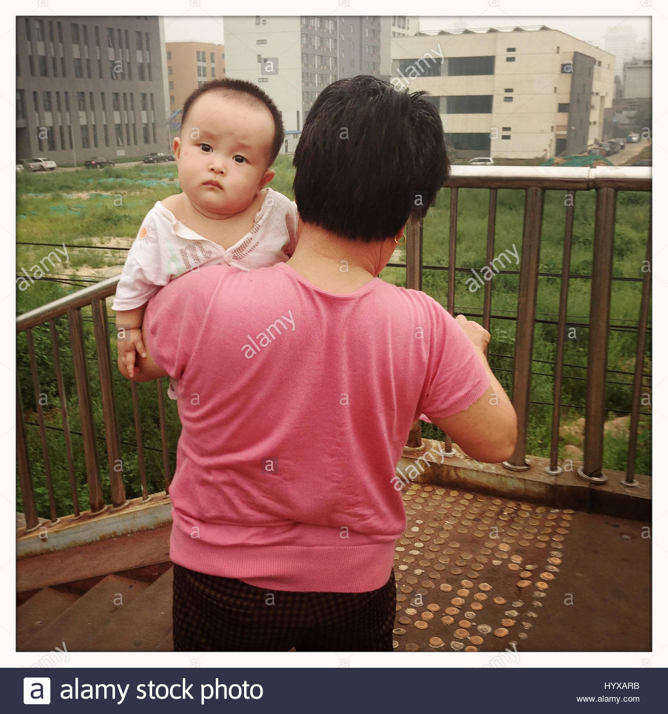 A woman holding a baby in the centre of Beijing. - Stock Image