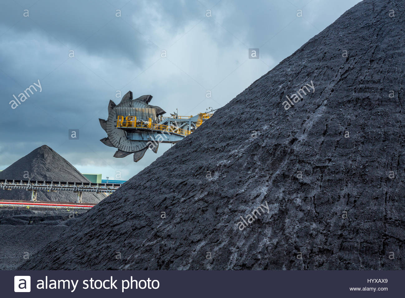 An automated bucket-wheel excavator loads coal into ships bound for China and India. - Stock Image