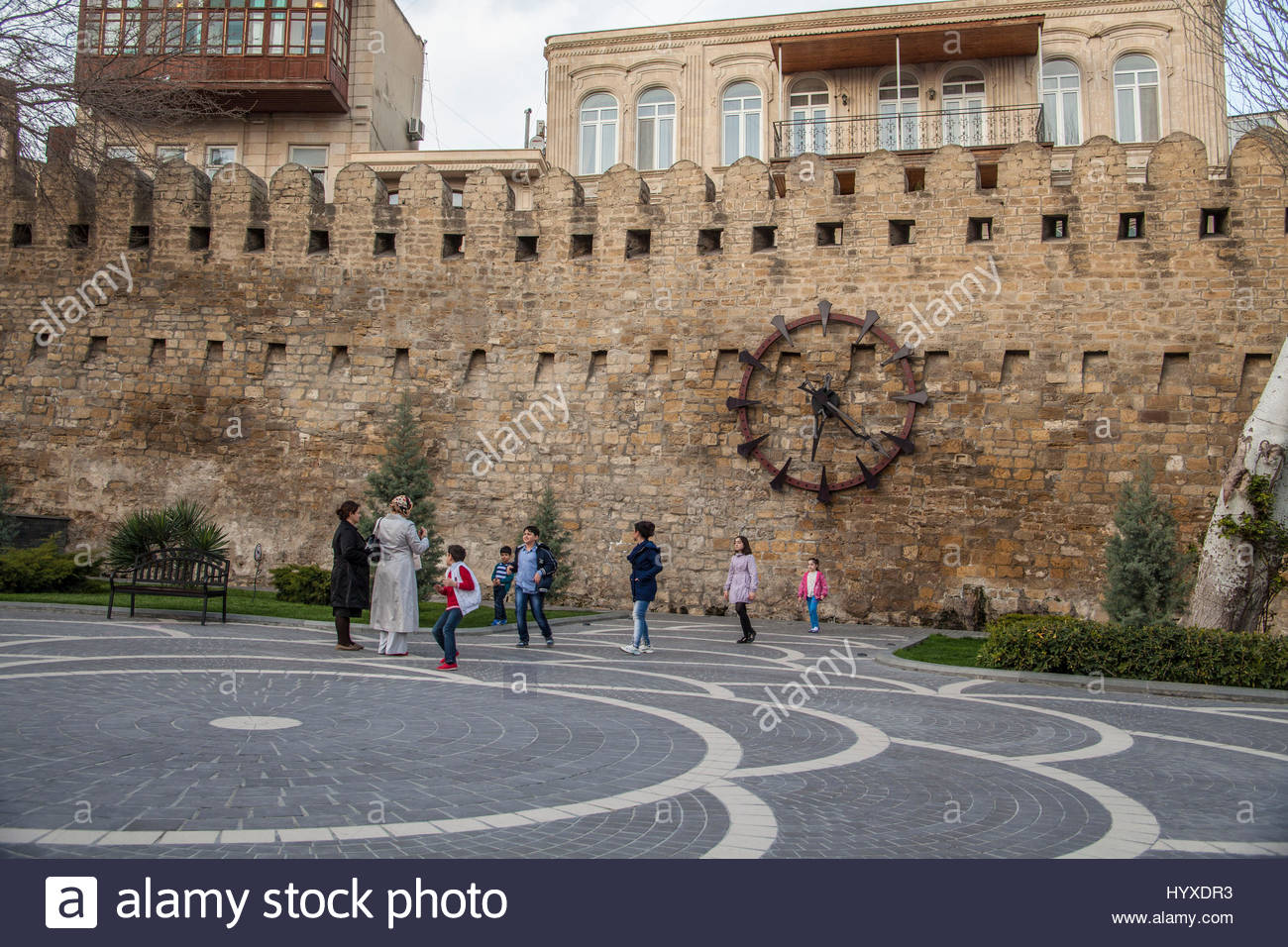 Pedestrians walk under the clock in Philharmony Park. - Stock Image