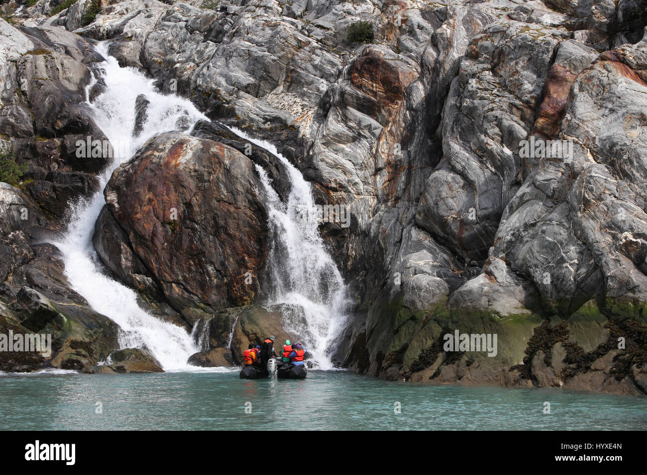Travelers in a Zodiak boat navigate near a waterfall that was formed from glacier runoff. - Stock Image