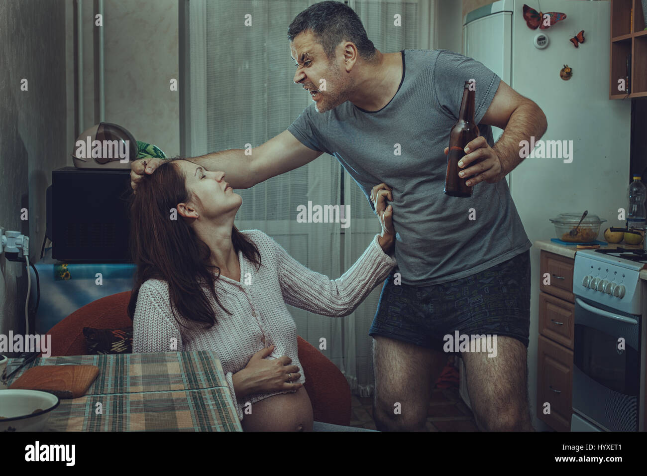 Alcoholic husband beats his wife, at home in the kitchen. Social problems of the family. - Stock Image