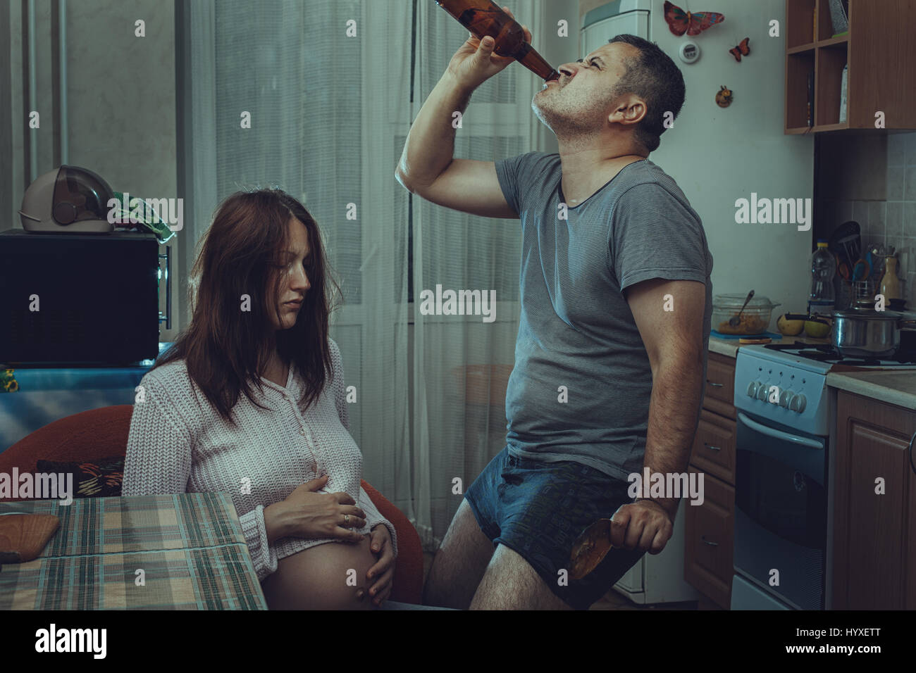 Sad pregnant wife, and next drink alcohol husband. Social problems of the family. - Stock Image