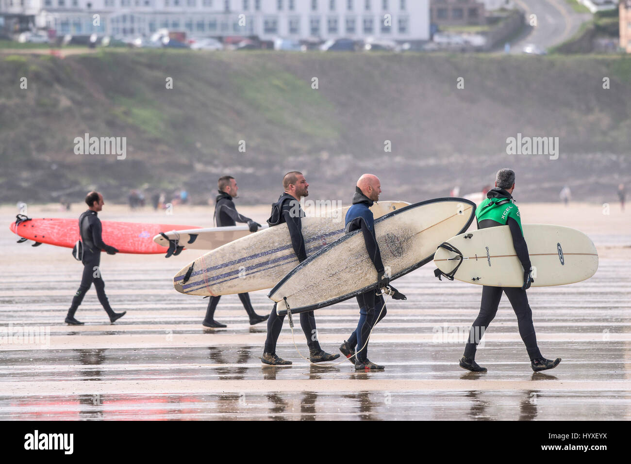 Surfers carrying surfboards Surfing UK Cornwall Walking Watersport Leisure activity Lifestyle Recreation Friends - Stock Image